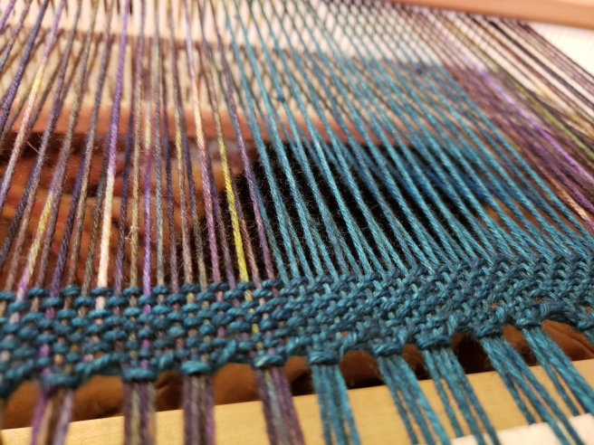 Close up of warp threads on a loom.