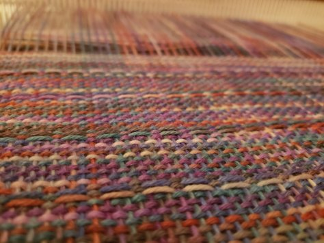 Close up shot of faint rainbow colored yarn worked up in a weaving pattern.