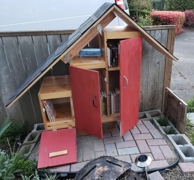 Front view of the Little Free Library, with the doors open - showing that they each open in a different direction, and giving a peek at the books inside.