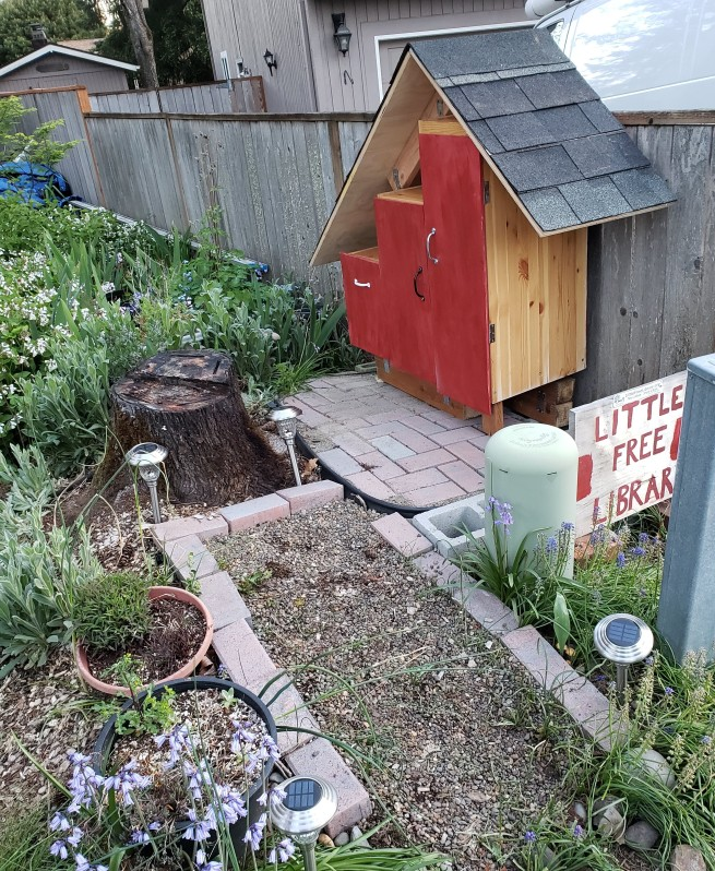 """Picture of a small structure with a peaked roof and three doors, each a different height in a stair-step pattern. The doors are painted red, and the structure is situated against a fence and on a small brick patio and gravel walkway leading up to it. To the side of the structure is a sign which reads """"Little Free Library."""""""
