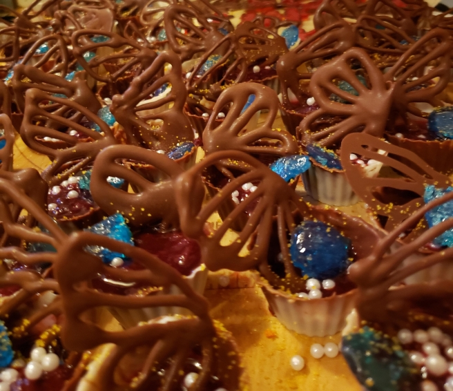 """A collection of chocolate cups, with a berry compote filling, blue """"gems"""" and chocolate """"butterfly wings."""""""