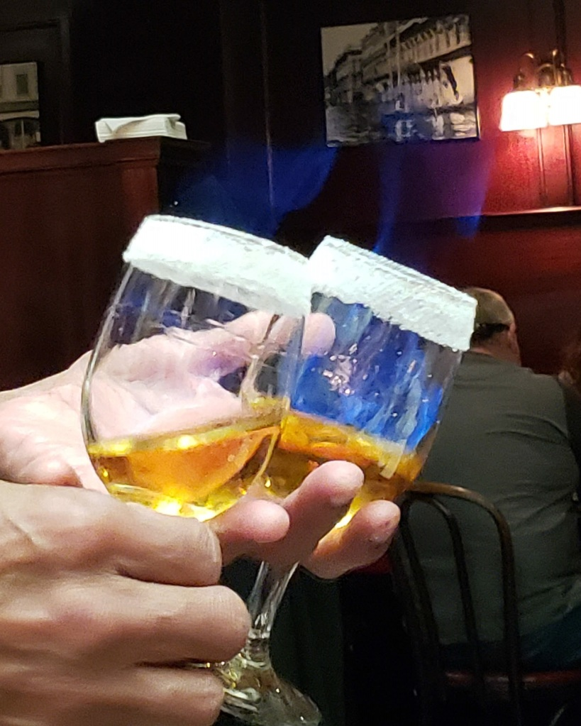 Close up image hands holding two wine glasses with an amber liquid in them, rimmed with glass. The blue flames of the fire on the rim of the glass are faintly visible.